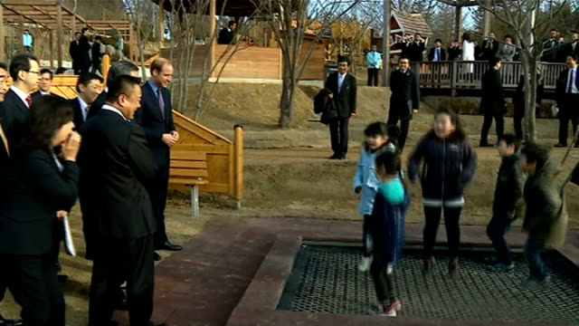 day 3 INT William juggling with soft balls at Smile Kid's Park as children and Shinzo Abe watch Children throwing balls at William William watching...