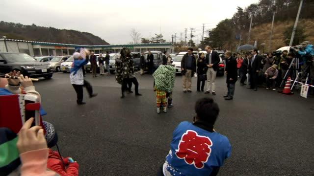 Ishinomaki and Onagawa JAPAN Ishinomaki and Onagawa Onagawa Crowds waving Union flags / Cars parked in car park / Shopping centre signage / Crowds /...