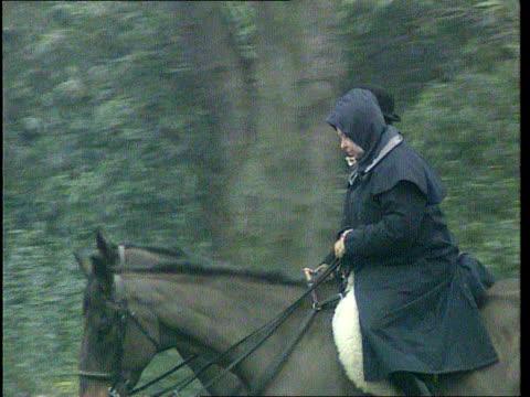 Sandringham Estate Queen along in wet weather gear riding horse next man