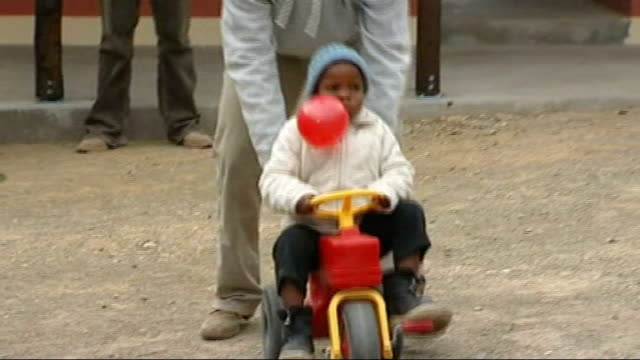Princes William and Harry take part in motorbike rally for charity R08070810 LESOTHO Prince Harry pushing small boy along on plastic tractor during...