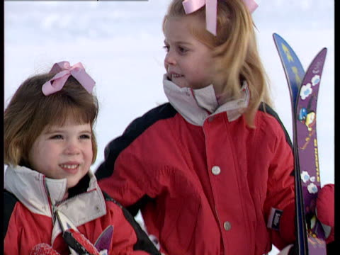 Princess Beatrice and Princess Eugenie sit in the snow during a skiing holiday in Klosters