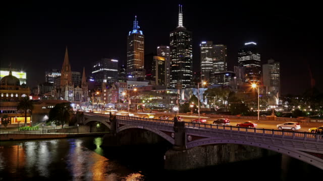 Princess Bridge day-night time lapse with Yarra River and Melbourne skyscrapers.