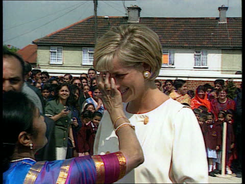 Princess of Wales Ethnic LIB Diana's bare feet TILT UP as Diana has red mark put on forehead Int SIDE Princess bends down to talk to children seated...