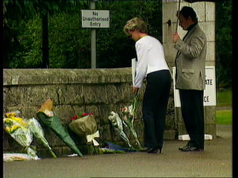 vídeos de stock e filmes b-roll de princess of wales: family at balmoral; kitn man and woman laying flowers at wall outside gatehouse - país de gales