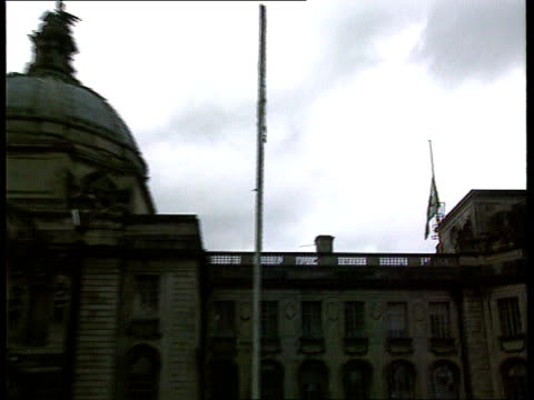 vídeos de stock e filmes b-roll de princess diana death; scotland: glasgow: city centre: bunches of flowers layed in city centre tilt up building wales: cardiff: city hall: welsh flag... - país de gales