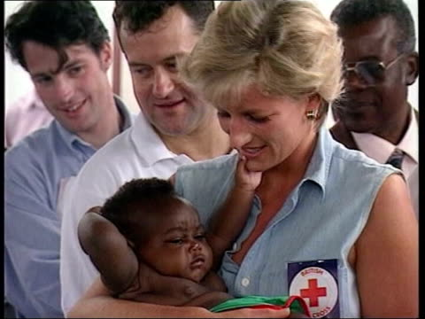 Princess Diana holding baby as standing next Burrell