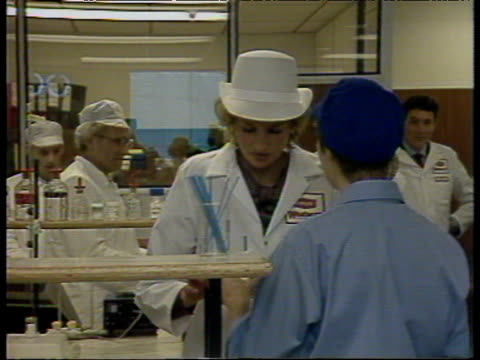 Princess Diana in white overalls and hat sips milk from carton during visit to dairy London 16 Sep 87
