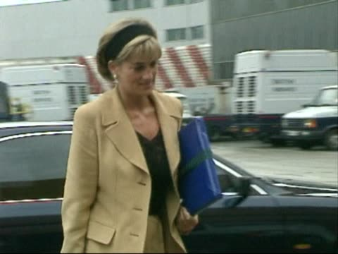 Princess Diana steps out of car and walks across brief stretch of Heathrow tarmac to aircraft service door to join flight to New York where she was...