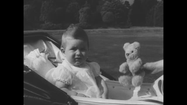princess elizabeth and philip, duke of edinburgh, push baby carriage containing prince charles on grounds of windlesham moor / charles and teddy bear... - britisches königshaus stock-videos und b-roll-filmmaterial