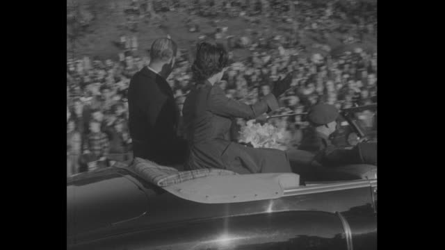 Princess Elizabeth and Prince Philip wave to crowds of children in TorontoÕs Riverdale Park from back of car / medium close up of kids cheering /...