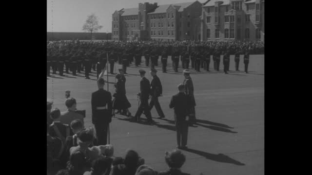 Princess Elizabeth and Prince Philp walk out onto parade ground of CanadaÕs Royal Military College with cadet escort / crowd looks on / cadets on...