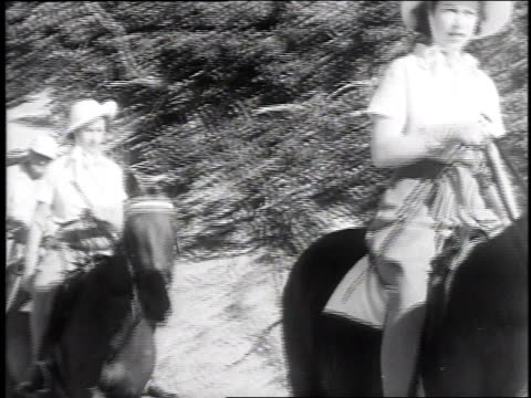 princess elizabeth and princess margaret on horseback emerging from a path and riding along the shore / united states - anno 1947 video stock e b–roll