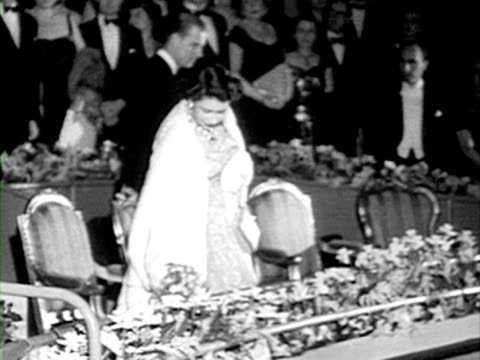 princess elizabeth and the duke of edinburgh taking their seats for the film premiere of les belles de nuit. 12 february 1953. - film premiere stock videos & royalty-free footage