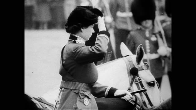 vídeos de stock, filmes e b-roll de / princess elizabeth as colonel in chief on horseback reviewing troops / guards on parade / young prince charles watches from window / guards parade... - 1951