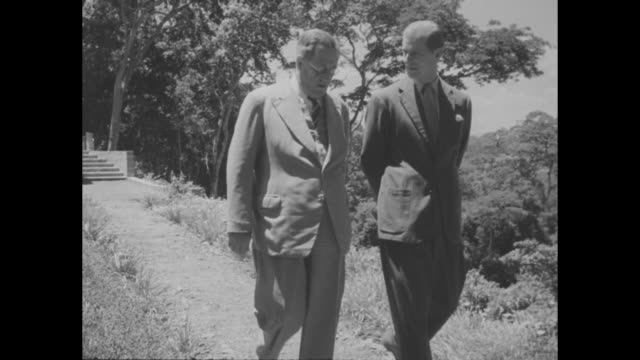 Princess Elizabeth Duchess of Edinburgh walks along path with Prince Philip Duke of Edinburgh following behind Sagana State Lodge in background /...