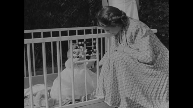 princess elizabeth kneels next to baby prince charles in playpen and they both play with tiny abacus on railing / different angle of charles and... - 1949 stock videos and b-roll footage