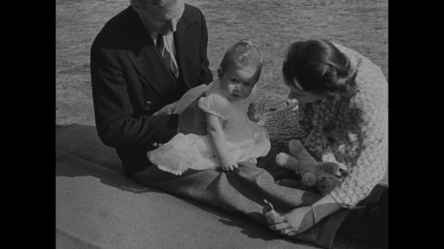 princess elizabeth prince charles and prince philip lie together on blanket on lawn / charles sits on philipís lap while elizabeth sits in front of... - duke of edinburgh stock videos and b-roll footage