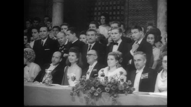 Princess Grace and Prince Rainier III sit in royal box / international group of debutantes in white parade around patio of the palace Pilates House /...