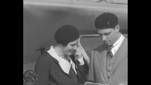 Princess Ileana of Romania and new husband Archduke Anton of Austria walk to plane taking them to Munich / both wearing berets discuss crossing the...
