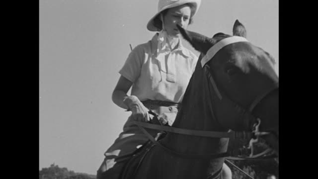 princess margaret gets onto a horse in background as princess elizabeth stands near her horse in foreground / montage margaret on the horse /... - königin elisabeth ii. von england stock-videos und b-roll-filmmaterial