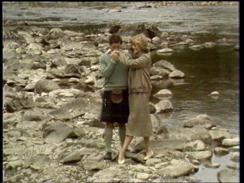 princess of wales agrees to divorce; ext/19.8.81 scotland: balmoral tlms charles and diana pose by river dee as he kisses her hand side press cms... - チャールズ皇太子点の映像素材/bロール