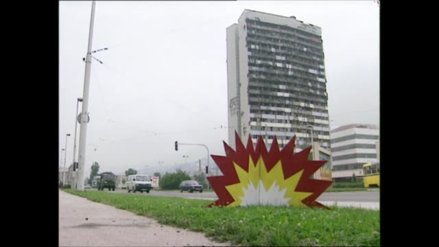 vidéos et rushes de princess of wales bosnia visit: arrival; bosnia and herzegovina: tuzla: posters on wall about landmines, gv bomb damaged building as traffic past,... - bosnie herzégovine