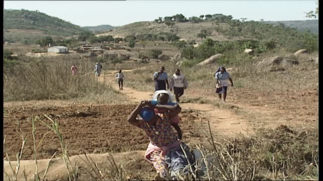 day three visit to ancient ruins zimbabwe feeding station nemazuva lgv huts of village people walking along track group of children waiting children... - malattia a trasmissione sessuale video stock e b–roll