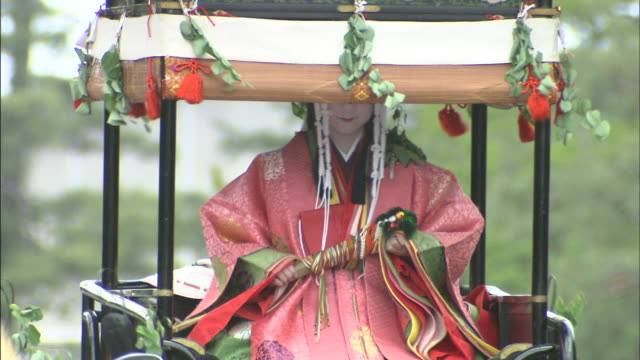 A princess rides on a parade float during the Hollyhock Festival.