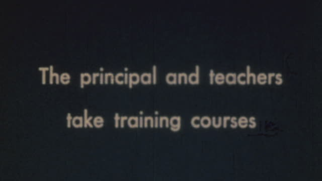 principal acting as air raid warden, pointing to blackboard and leading training course on air raid drill, and teachers writing on pads on their laps... - allarme di prova video stock e b–roll
