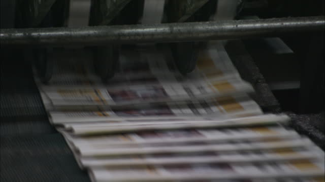 printed and folded newspapers shoot out of a machine at a rapid pace. - south america stock videos & royalty-free footage