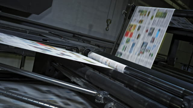 slo mo printed paper travelling across rollers in the printing press - paper industry stock videos & royalty-free footage