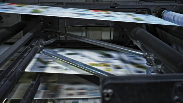 vidéos et rushes de ld papier imprimé voyageant rapidement à travers la presse du journal - imprimerie