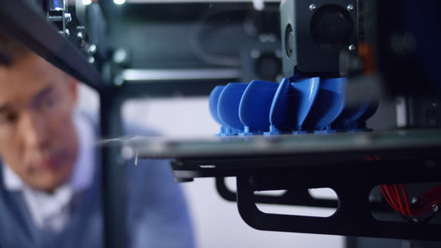 3d printer constructing a model of a propeller and asian male engineer overlooking the progress - concept stock videos & royalty-free footage