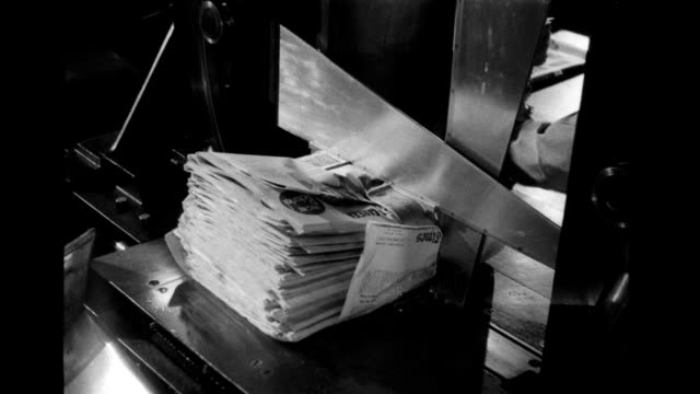 printing press and production facilities, man puts stack of newspapers into machine which binds/ties them into a bundle. newspaper bundling machine... - printing press stock videos & royalty-free footage
