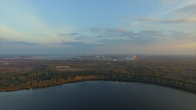 pripyat abandoned town near chernobyl nuclear power plant. flight rightside above the water of yanovsky zaton lake with a view to chnpp - 1986 stock videos and b-roll footage