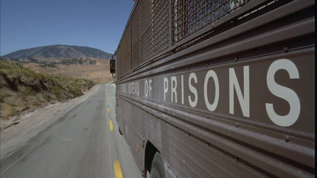 A prison bus drives down a desert road.