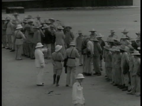 vidéos et rushes de prison camp building w/ men standing outside. officials lining prisoners up, one male calling roll, prisoners or exiles standing, male giving water... - dom tom