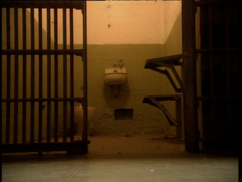 prison cell gate is closed as guard's feet walk past camera. toilet and wash basin visible in cell through bars. alcatraz prison - jail cell stock videos & royalty-free footage