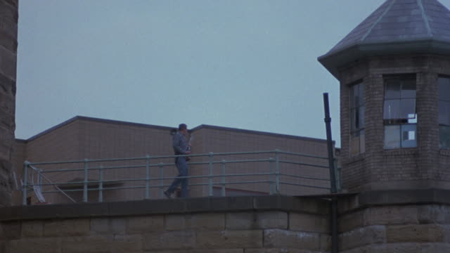 a prison guard is pacing back and forth on the roof of a prison near a watchtower. - prison guard stock videos and b-roll footage