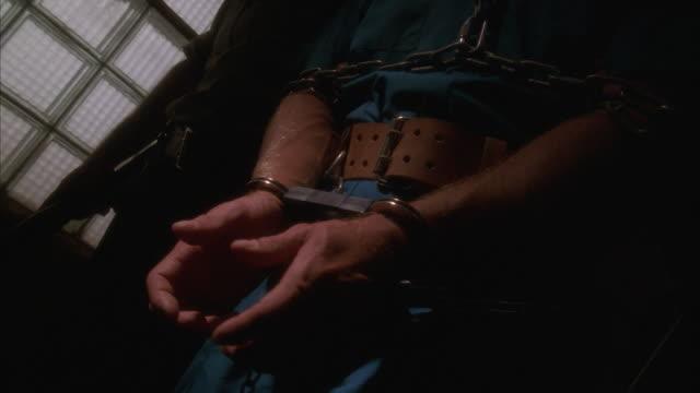 vídeos de stock, filmes e b-roll de ecu, slo mo, prison guard leading male prisoner in chains (mid section) - algema