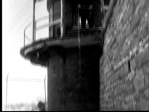 1956 la td prison guard on watch tower lowering key on string to man on snowy below at kansas state penitentiary/ tu guard/ lansing, kansas - kansas stock videos & royalty-free footage