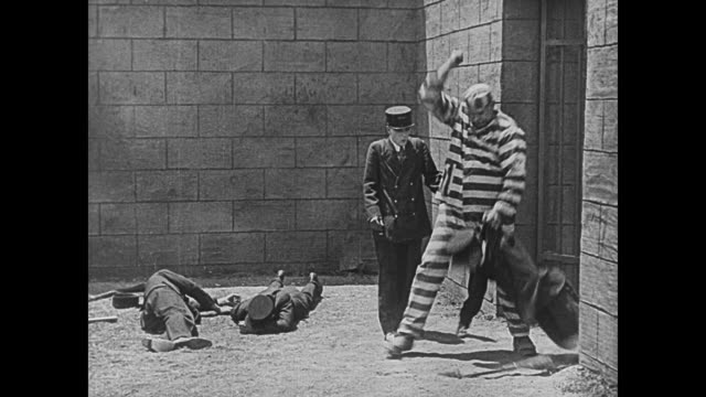 1920 prison guard (buster keaton) thinks he's jailed bully convict (joe roberts) - uniform stock-videos und b-roll-filmmaterial