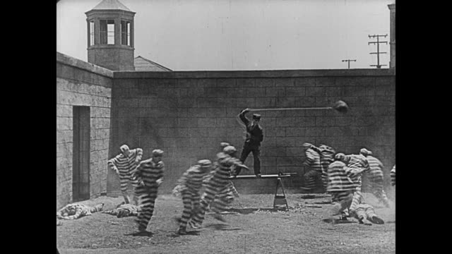 stockvideo's en b-roll-footage met 1920 prison guard (buster keaton) uses punching bag to quell riot - stootzak fitnessapparatuur