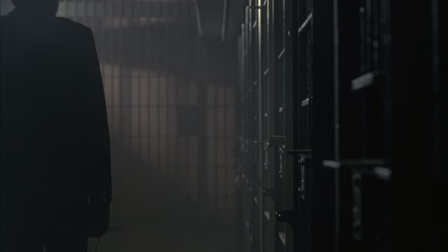 a prison guard walks by a cell where a prisoner's arms  rest on the bars as smoke from his cigarette hangs in the air. - 囚人点の映像素材/bロール