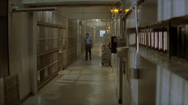 vídeos y material grabado en eventos de stock de a prison guard walks down a hallway between cells. - celda de cárcel