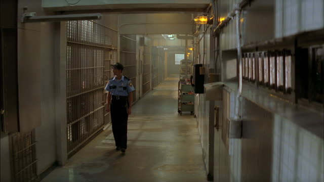 a prison guard walks down a hallway between cells. - prison stock videos & royalty-free footage