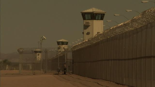 a prison guard walks through a gate. - prison guard stock videos & royalty-free footage