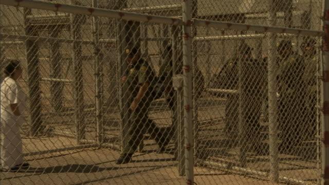 prison guards enter a prison yard through a gate. - prison guard stock videos & royalty-free footage
