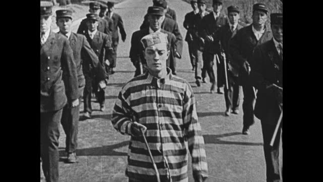 1920 prison guards follow and march with man (buster keaton) in convict clothes - uniform stock-videos und b-roll-filmmaterial