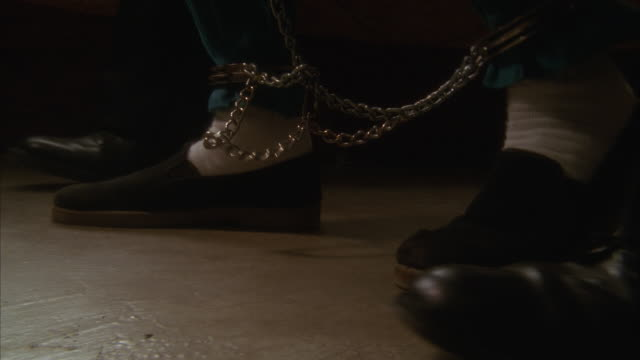 vídeos de stock, filmes e b-roll de ecu, slo mo, prison guards leading male prisoner in leg chains (low section) - prisoner